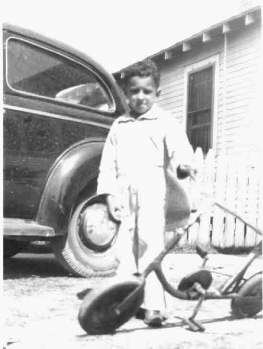 Photo of Buster's first car, 1940 Chevy and Bobby's first bike, boy is Dale Boudreaux, c.1945